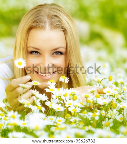 Beautiful woman enjoying daisy field, nice female lying down in the meadow of flowers, pretty girl relaxing outdoor, having fun,holding plant, happy young lady and spring green nature, harmony concept - stock photo
