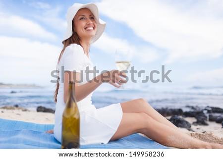 Beautiful woman enjoying glass of wine on the beach - stock photo