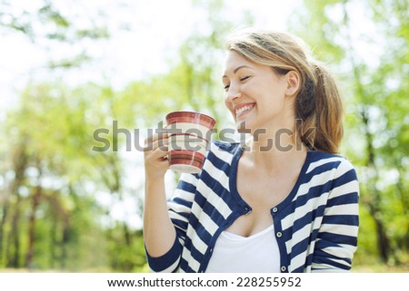 Beautiful woman enjoying her cup of tea after doing yoga exercise. - stock photo