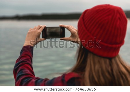 Beautiful woman enjoying her day taking pictures with her phone