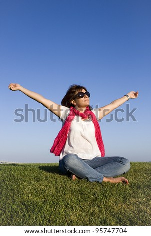 Beautiful woman enjoying life with her arms outstretched - stock photo