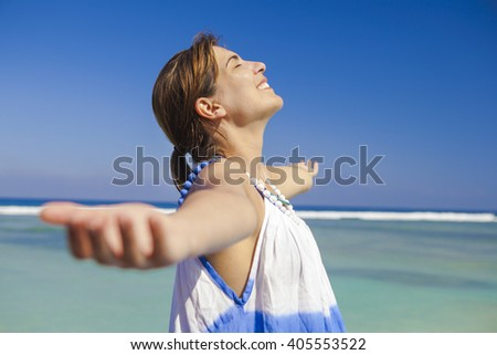 Beautiful woman enjoying the summer with both arms open - stock photo