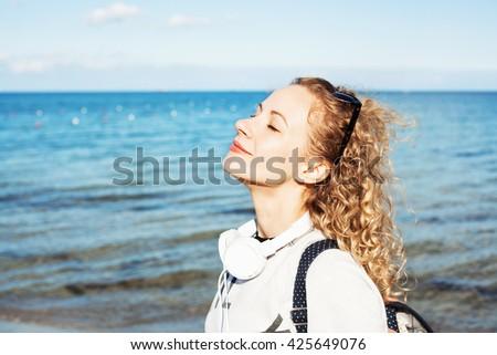 Beautiful woman enjoying with a fresh sea breeze - stock photo