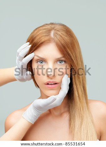beautiful woman examined by plastic surgeon - stock photo
