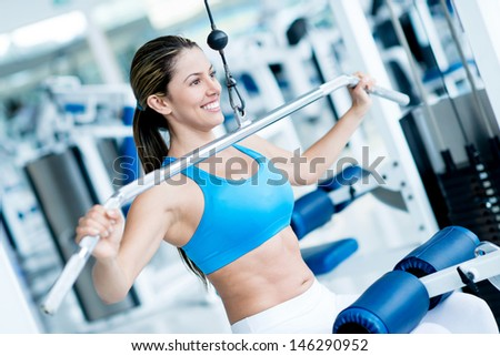 Beautiful woman exercising at the gym on a machine  - stock photo