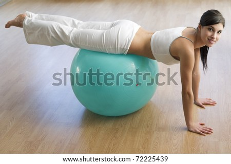 Beautiful woman exercising with ball - stock photo