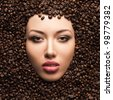 Beautiful woman face in coffee beans - stock photo