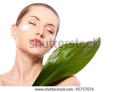 beautiful woman  face portrait with green leaf and cream on face, closed eyes - stock photo