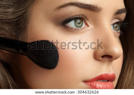 Beautiful woman face powders, and apply blush to the cheekbones - stock photo