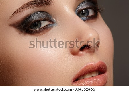 Beautiful woman face with bright make up eye with sexy liner makeup. Fashion big arrow shape on woman's eyelid. Chic evening make-up, healthy face