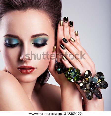Beautiful woman face with green make-up and glass jewelry, creative nails - stock photo