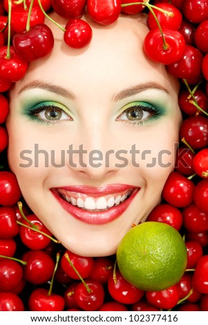 beautiful woman face with red ripe big fresh cherry and lime frame - stock photo