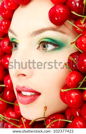 beautiful woman face with red ripe big fresh cherry frame - stock photo