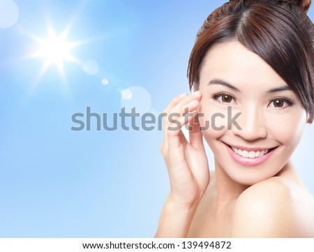 Beautiful woman face with sunshine and blue sky, concept for summer skin care and sun block, asian beauty