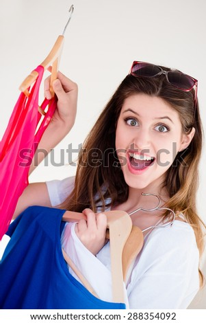Beautiful woman faced with choices while shopping  - stock photo