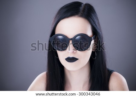Beautiful woman fashion model portrait in sunglasses with black lips and earrings. Creative hairstyle and make up. Beauty girl on a gray background - stock photo