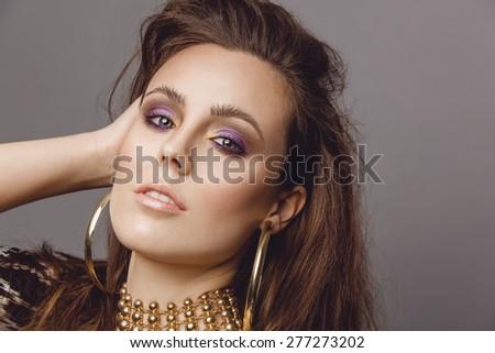 Beautiful woman, fashion model posing with smokey eyes, glossy lipstick and shiny skin. Studio portrait with copy space. - stock photo