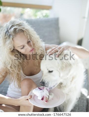Beautiful woman feeding cake to dog in house - stock photo