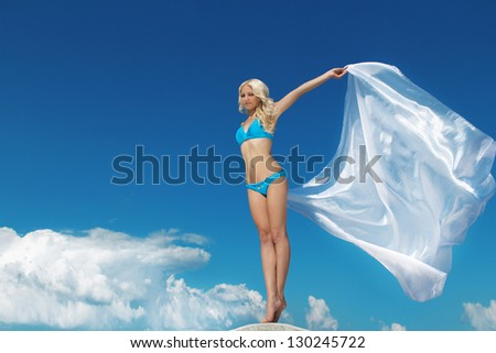 Beautiful woman feeling free against blue sky with blowing fabric. Travel and Vacation. Freedom Concept