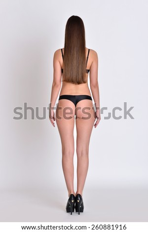 Beautiful woman fill length lateral side in black underwear in studio with grey background. Not object.