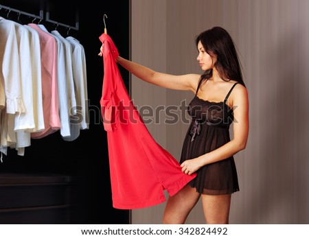beautiful woman fits on a red dress in the shopping mall - stock photo