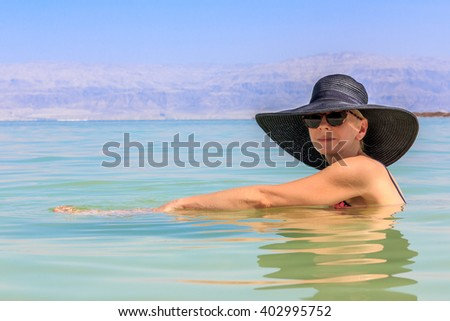 Beautiful woman floating in the waters of the Dead Sea, Israel - stock photo