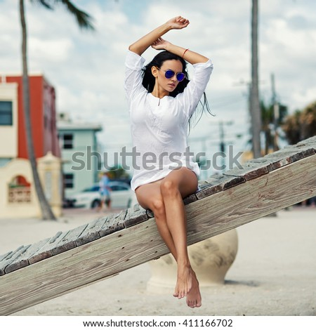 Beautiful woman full body portrait sit on a lifeguard tower. Hollywood beach in Miami, florida. Filtered image. - stock photo