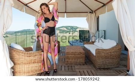 Beautiful woman full body portrait wearing black lingerie in a gazebo. - stock photo