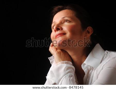 Beautiful woman gazing upward with a feeling of joyful contentment - stock photo