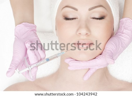Beautiful woman gets an injection in her face isolated on white