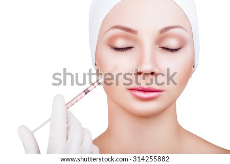 Beautiful woman gets an injection in her face isolated on white background - stock photo