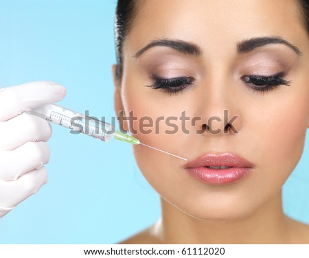 Beautiful woman gets injection in her face - stock photo