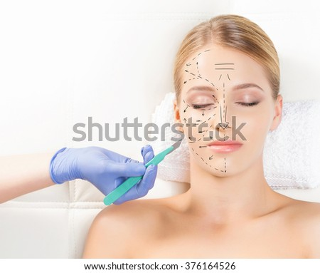 Beautiful woman getting face lifting operation. Drawing arrows and a scalpel over her face. Aging and plastic surgery concept. - stock photo