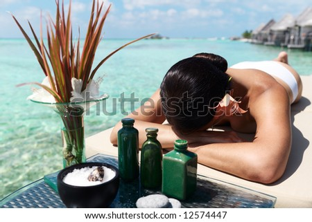 Beautiful woman getting spa treatment at daylight near the ocean. Focus on woman - stock photo