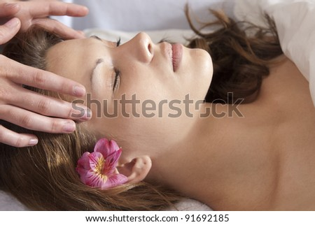 Beautiful woman getting temples massaged at spa. - stock photo