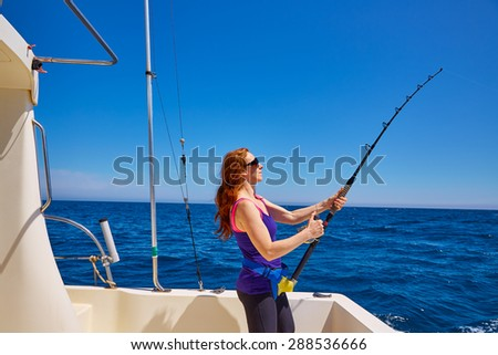 Beautiful woman girl fishing rod trolling in saltwater in a boat trolling - stock photo