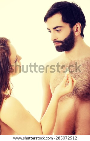 Beautiful woman giving a condom to her handsome man. - stock photo
