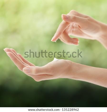 Beautiful Woman Hands Applying Cream - stock photo