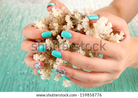 Beautiful woman hands with blue manicure holding coral, on color background - stock photo