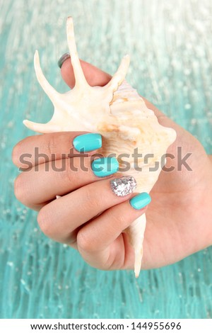 Beautiful woman hands with blue manicure holding shell, on color background - stock photo