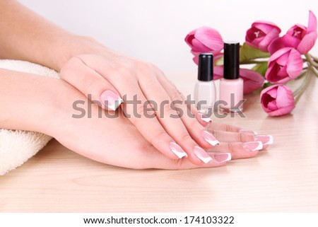 Beautiful woman hands with french manicure and flowers on table on white background - stock photo