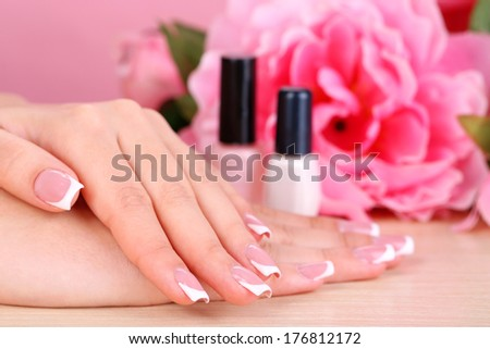 Beautiful woman hands with french manicure and flowers on wooden background - stock photo
