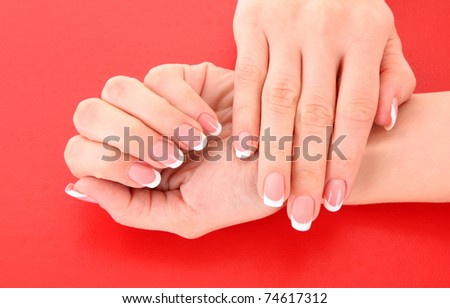 Beautiful woman hands with french manicure on red background - stock photo