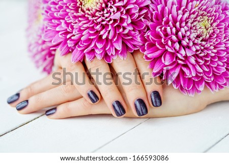 Beautiful woman hands with manicure lying down during spa treatment with delicate pink flowers - stock photo