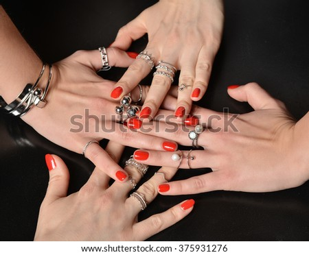 Beautiful woman hands with red pattern polish manicured nails and silver stacking rings and bracelets eating abstract pearl - stock photo