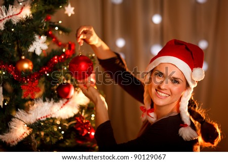 Beautiful woman hanging toy on Christmas tree - stock photo