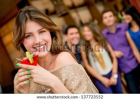 Beautiful woman having a cocktail at the bar - stock photo