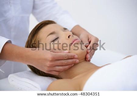 Beautiful woman having a facial massage - stock photo