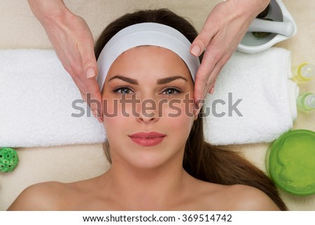Beautiful woman having a facial massage beauty treatment - stock photo