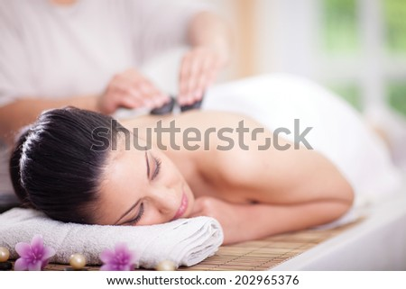 Beautiful woman having a wellness back massage - stock photo
